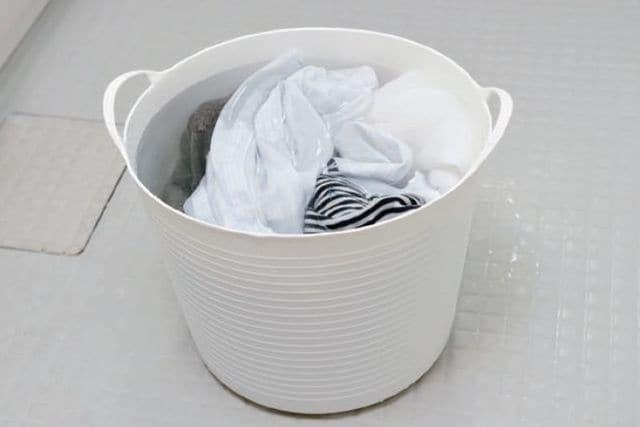 汚れものを入れておく洗濯かご代わりに、オキシ溶液の入ったバケツを用意しておくだけ!(写真:『ほったらかし掃除術』)